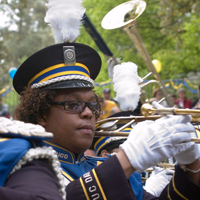 Woman in marching band uniform and hat with a trumpet