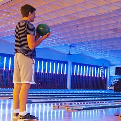 Man standing with a bowling ball eying his lane