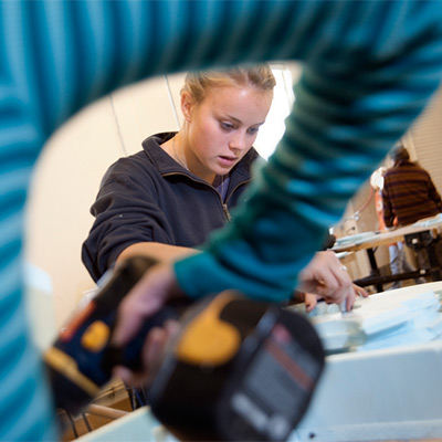 Woman working on a sculpture seen through the elbow area of a woman holding a drill